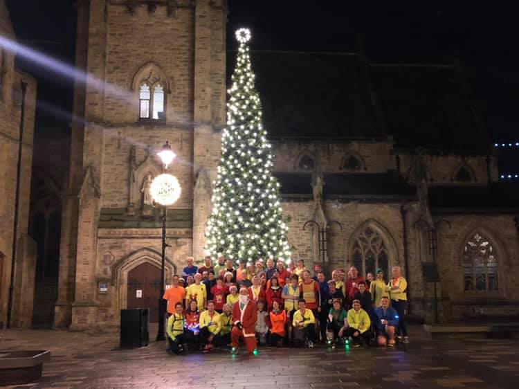 Club photo in market square of Striders with Christmas Tree in background.  photo credit: Jonathan Hamill