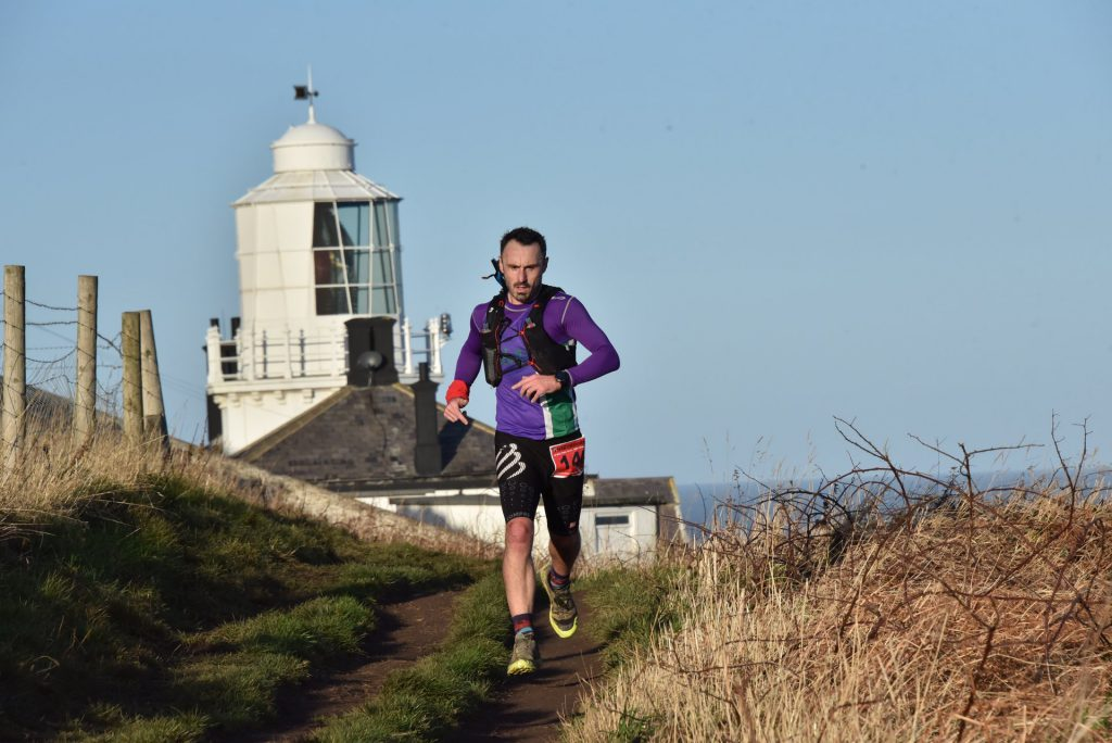 Mark Kearney running along coastal path with lighthouse behind him.